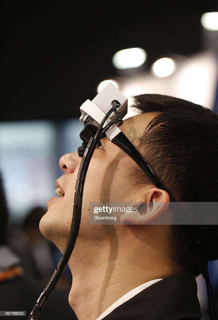 A visitor tests a concept 'Viking' head mounted display device on the Brilliantservice Co. stand at the Mobile World Congress in Barcelona, Spain, on Tuesday, Feb. 26, 2013. The Mobile World Congress, where 1,500 exhibitors converge to discuss the future of wireless communication, is a global showcase for the mobile technology industry and runs from Feb. 25 through Feb. 28. Photographer: Simon Dawson/Bloomberg via Getty Images