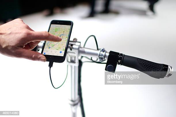 A visitor tests a map navigation system on a smartphone attached to the handlebars of a Ford MoDeMe foldable electric ebike in the Ford Motor Co...