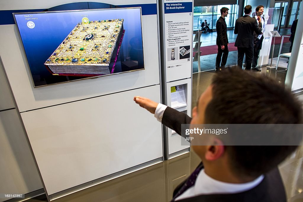 A visitor tests an interactive 3-D boook explorer at Fraunhofer stand at the 2013 CeBIT technology trade fair on March 5, 2013 in Hanover, Germany. CeBIT will be open March 5-9.