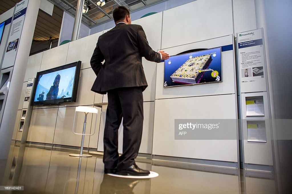 A visitor tests an interactive 3-D boook explorer at Fraunhofer stand at the 2013 CeBIT technology trade fair on March 5, 2013 in Hanover, Germany. CeBIT will be open March 5-9. AFP PHOTO / CARSTEN KOALL