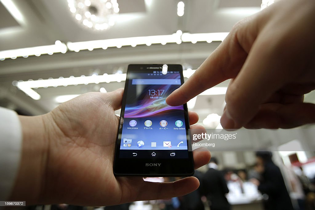 A visitor tests an NTT DoCoMo Inc. Xperia Z SO-02E smartphone, manufactured by Sony Corp., during a product launch in Tokyo, Japan, on Tuesday, Jan. 22, 2013. NTT DoCoMo, Japan's biggest mobile-phone company, released their latest tablet and smartphone series today. Photographer: Kiyoshi Ota/Bloomberg via Getty Images