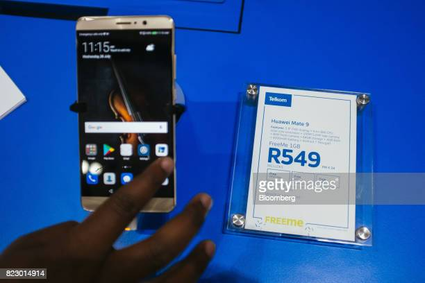 A visitor tests the functions on a Huawei Technologies Co Ltd Mate 9 smartphone inside a phone store operated by Telkom SA SOC Ltd in Pretoria South...