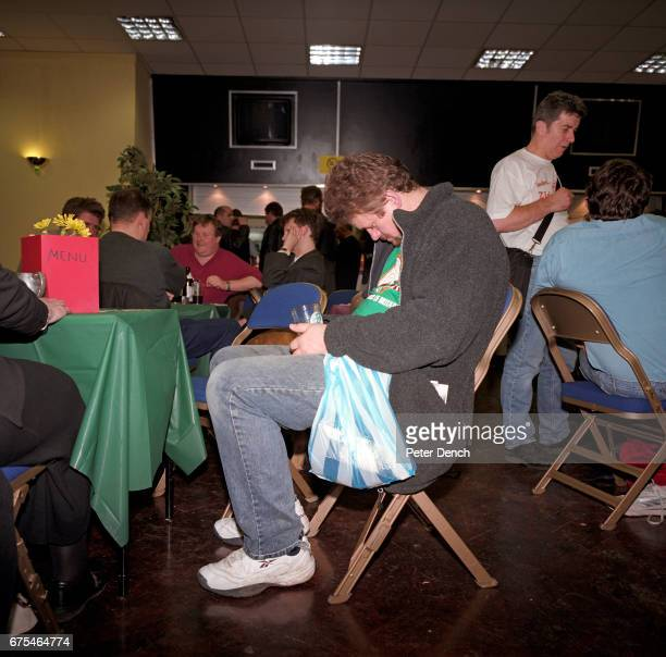 A visitor to a CAMRA beer festival in north London takes a nap in his seat March 2001