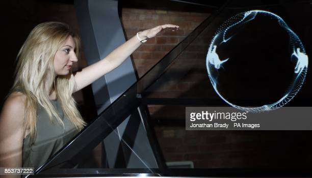 A visitor to a showcase of 3D technology manipulates the Conran designed 'HOLO' the world's first gesture interactive hologram display at the FLUX...