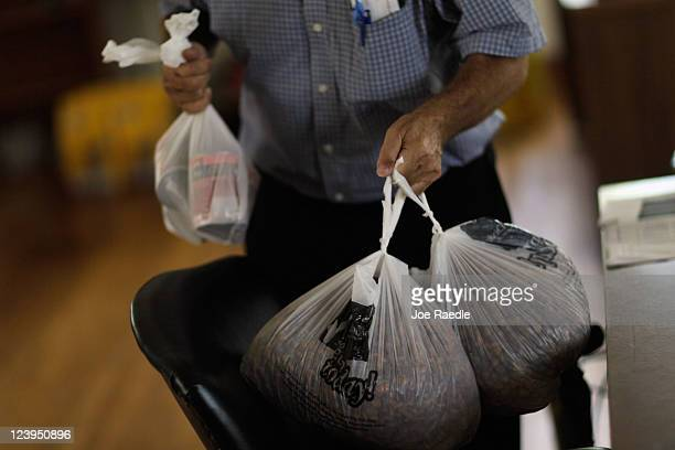 A visitor to Fido's Food Bank at the Peggy Adams Animal Rescue League carries bags of dog food to his car September 6 2011 in Palm Beach Florida As...