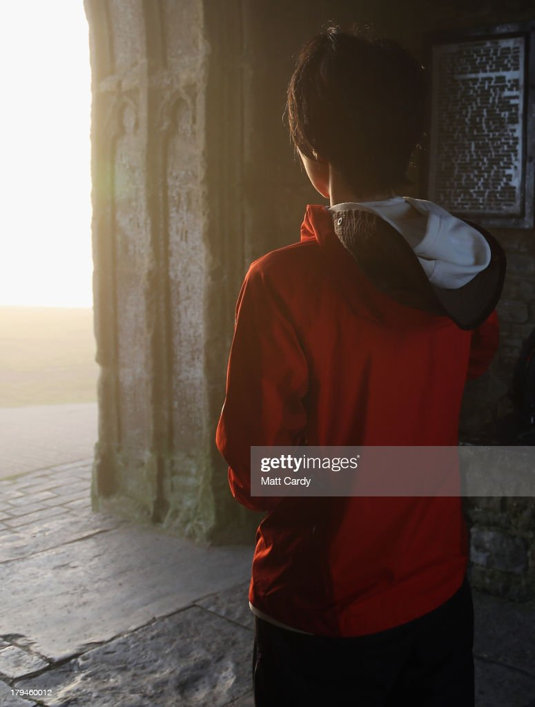 A visitor to Glastonbury Tor meditates inside St. Michael's Tower, a ruined 14th-century church tower, as the rising sun begins to clear the early morning mist and fog near the town of Glastonbury on September 4, 2013 in Somerset, England. Parts of the UK are set to enjoy a late summer heatwave today, with temperatures possibly reaching 28C in central, eastern and southern England, with temperatures predicted to climb even higher tomorrow.