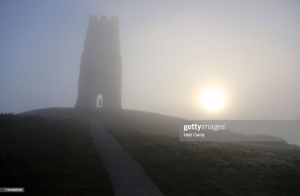 A visitor to Glastonbury Tor stands inside St. Michael's Tower, a ruined 14th-century church tower, as the rising sun begins to clear the early morning mist and fog near the town of Glastonbury on September 4, 2013 in Somerset, England. Parts of the UK are set to enjoy a late summer heatwave today, with temperatures possibly reaching 28C in central, eastern and southern England, with temperatures predicted to climb even higher tomorrow.
