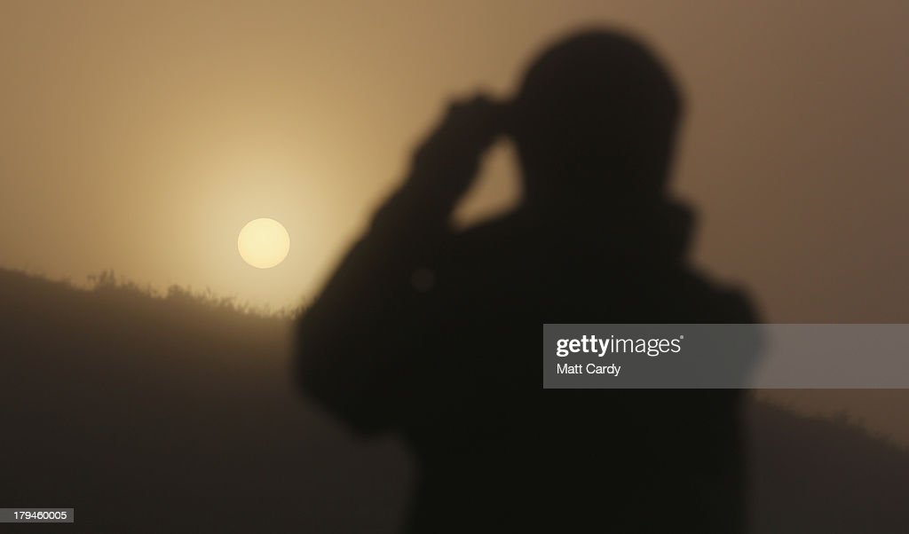 A visitor to Glastonbury Tor takes a photograph of St. Michael's Tower, a ruined 14th-century church tower, as the rising sun begins to clear the early morning mist and fog near the town of Glastonbury on September 4, 2013 in Somerset, England. Parts of the UK are set to enjoy a late summer heatwave today, with temperatures possibly reaching 28C in central, eastern and southern England, with temperatures predicted to climb even higher tomorrow.