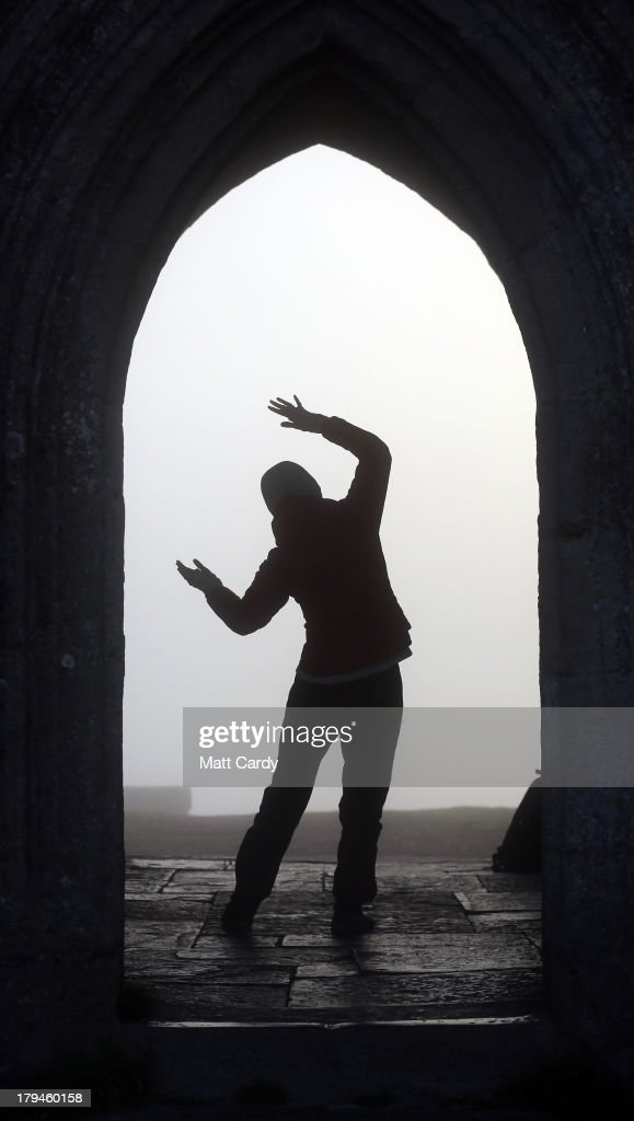A visitor to Glastonbury Tor welcomes the sun rise as she stands inside St. Michael's Tower, a ruined 14th-century church tower, as the rising sun begins to clear the early morning mist and fog near the town of Glastonbury on September 4, 2013 in Somerset, England. Parts of the UK are set to enjoy a late summer heatwave today, with temperatures possibly reaching 28C in central, eastern and southern England, with temperatures predicted to climb even higher tomorrow.