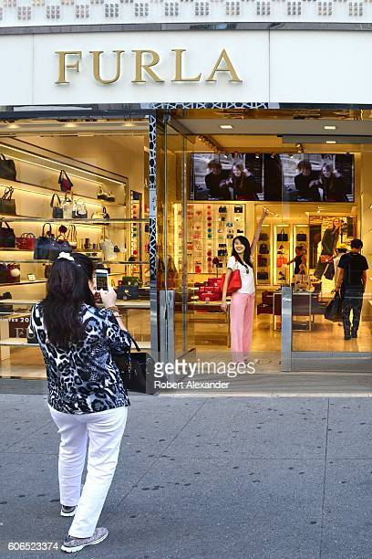 A visitor to New York City strikes a pose at the entrance to the Furla store on Fifth Avenue on August 27 2016 The Italian womens' accessories shop...