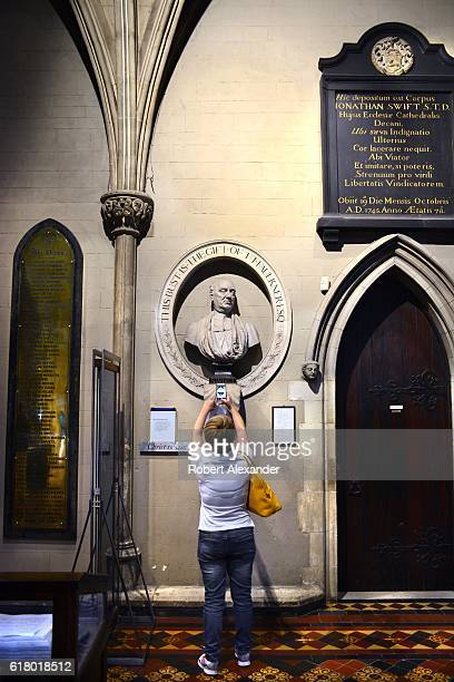A visitor to St Patrick's Cathedral in Dublin Ireland photographs a bust of Jonathan Swift who was the cathedral's dean from 1713 until his death in...