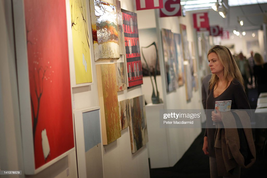 A visitor to The Affordable Art Fair looks at paintings on March 15, 2012 in London, England. 120 galleries are displaying works costing from £40 - £4000. Photography, paintings, prints and sculptures are on sale from 15-18th March 2012.