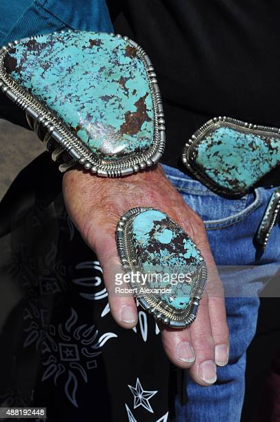 A visitor to the annual Santa Fe Indian Market in Santa Fe New Mexico wears oversized Navajo jewelry and fashion accessories including a turquoise...