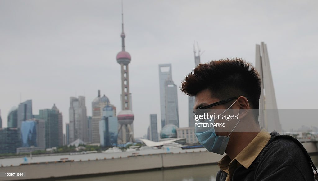 A visitor to the historic Bund district in Shanghai wears a facemask on April 19, 2013. Experts from the UN's health agency arrived in China on a weeklong mission in Beijing and Shanghai to examine whether the H7N9 bird flu virus is spreading among humans after a cluster of cases among relatives but downplayed fears of a pandemic on April 19. AFP PHOTO/Peter PARKS