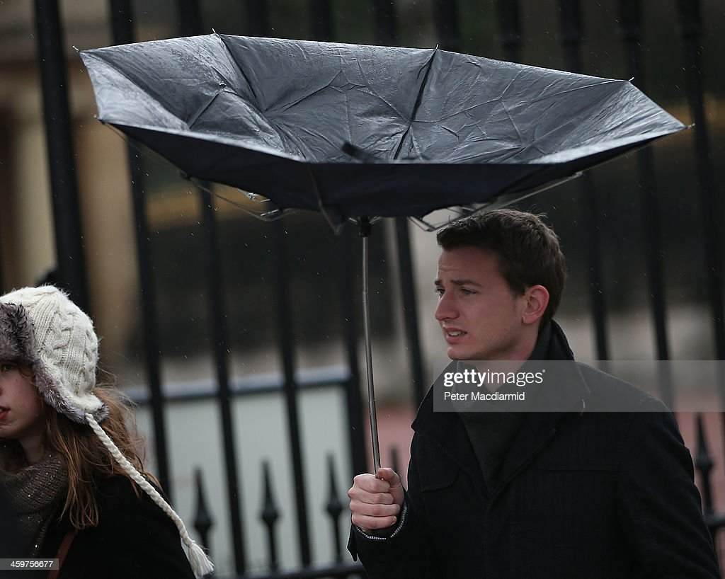 A visitor to The Mall struggles with an umbrella in wet and windy conditions on December 30, 2013 in London, England. Parts of the United Kingdom are experiencing wintry conditions.