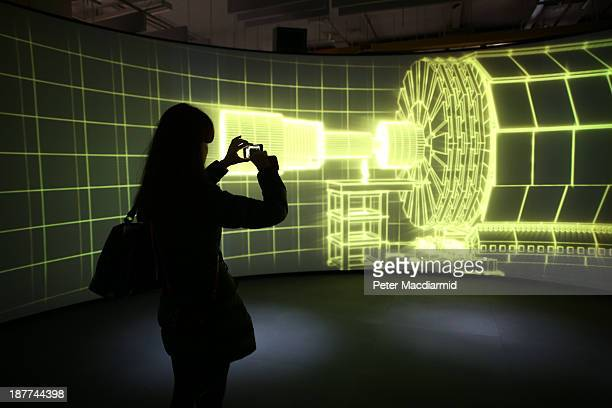 A visitor to the Science Museum takes a phone photograph of a video projection showing the workings of the Large Hadron Collider at the 'Collider'...