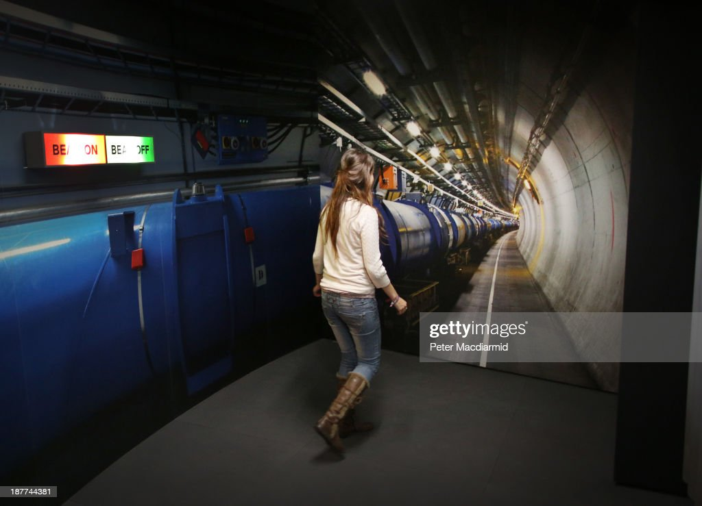 A visitor to the Science Museum walks towards a photograph of the workings of the Large Hadron Collider (LHC) at the 'Collider' exhibition on November 12, 2013 in London, England. At the exhibition, which opens to the public on November 13, 2013 visitors will see a theatre, video and sound art installation and artefacts from the LHC, providing a behind-the-scenes look at the CERN particle physics laboratory in Geneva. It touches on the discovery of the Higgs boson, or God particle, the realisation of scientist Peter Higgs theory.