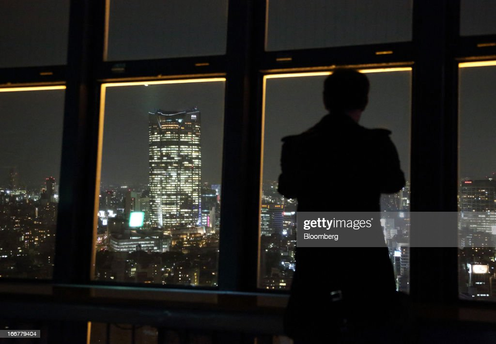 A visitor to the Tokyo Tower looks at the Roppongi Hills Mori Tower, operated by Mori Building Co., at the tower's observatory at night in Tokyo, Japan, on Tuesday, April 17, 2013. While financial firms have cut staff in Japan, technology companies have boosted hiring, and as bankers vacated offices at Roppongi Hills, companies including Google Inc. and Lenovo Group Ltd. moved in. As early as this month, Apple Inc. will also make the complex its home in Japan, two people familiar with the plan said in January. Photographer: Tomohiro Ohsumi/Bloomberg via Getty Images