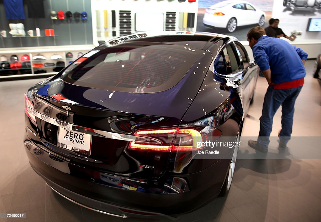 A visitor to theTesla Motors showroom looks at a vehicle at the Dadeland Mall on February 19, 2014 in Miami, Florida. Tesla said today it earned $46 million in the fourth quarter on a non-adjusted basis, or 33 cents a share, causing shares in the company to jump 12 percent.