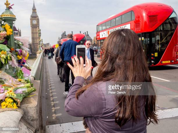 A visitor to Westminster Bridge in London takes a photograph on her phone of a floral tribute left for victims of the terror attack in Westminster on...