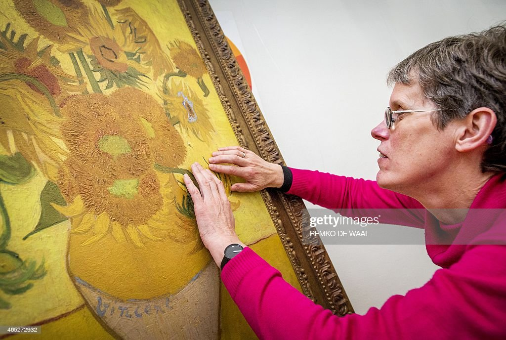 A visitor touches a 3D reproduction of the famous painting Sunflowers by late Dutch artist Vincent van Gogh during a guided tour for visually...