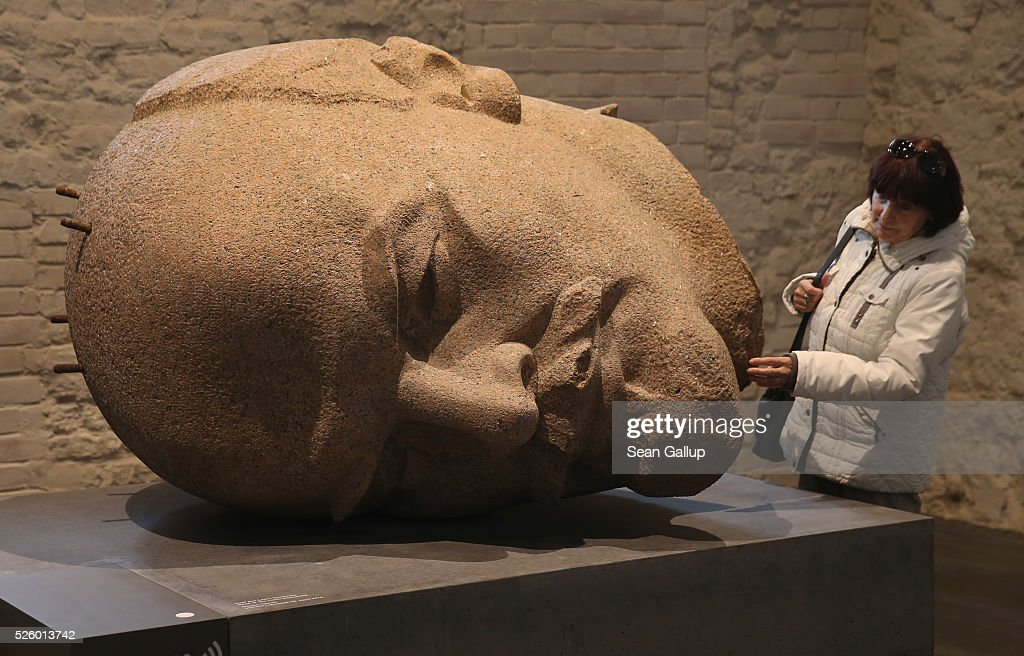 A visitor touches a bust of Russian revolutionary Vladimir Lenin at the exhibition: 'Uncovered. Berlin and its Monuments' ('Enthuellt. Berlin und seine Denkmaeler') at the Spandau citadel on April 29, 2016 in Berlin, Germany. The statue of Lenin was over 19 meters tall and stood on Lenin Square in communist East Berlin before being removed by authorities after 1989, broken up into pieces and buried in a forest outside Berlin. The exhibition shows about 100 monuments that have been damaged, removed or stored away over the years and together guide visitors through the history of th city. The exhibition will run until October 30.