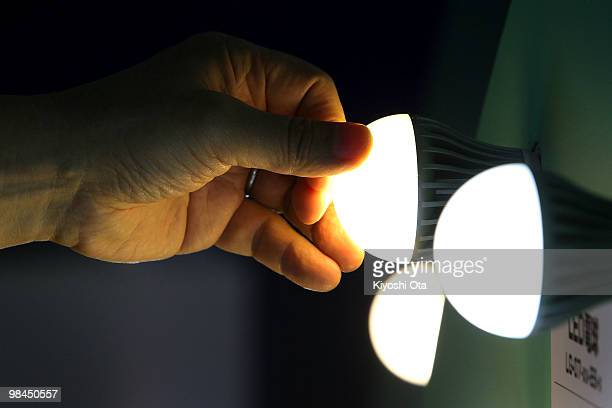 A visitor touches a light emitting diode bulb during the second LED/OLED Lighting Technology Expo 'LIGHTING JAPAN' at Tokyo Big Sight on April 14...