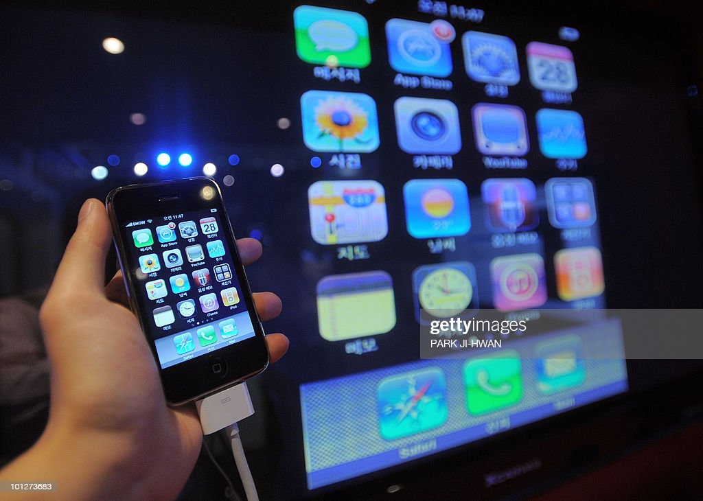 A visitor touches a smart phone during the World IT Show in Seoul on May 28, 2010.
