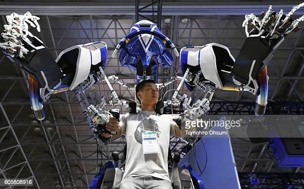 A visitor tries a Skeletonics exoskeleton suit as he plays the FigureHeads online game in the Intel Corp booth at the Tokyo Game Show 2016 on...