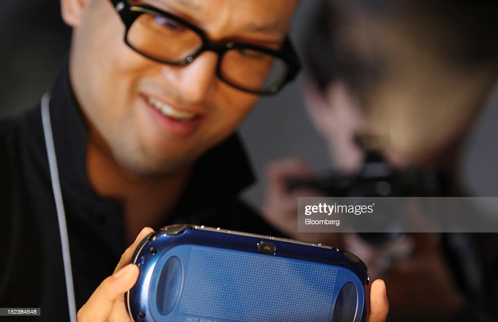 A visitor tries a Sony Computer Entertainment Inc. PlayStation Vita handheld game player at the Tokyo Game Show 2012 at Makuhari Messe in Chiba, Japan, on Thursday, Sept. 20, 2012. The show will be held through Sept. 23. Photographer: Tomohiro Ohsumi/Bloomberg via Getty Images