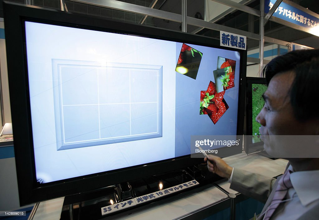 A visitor tries a touch panel screen displayed at the Finetech Japan exhibition in Tokyo, Japan, on Wednesday, April 11, 2012. Finetech Japan, the world's largest flat panel display exhibition, will be held through April 13. Photographer: Tomohiro Ohsumi/Bloomberg via Getty Images