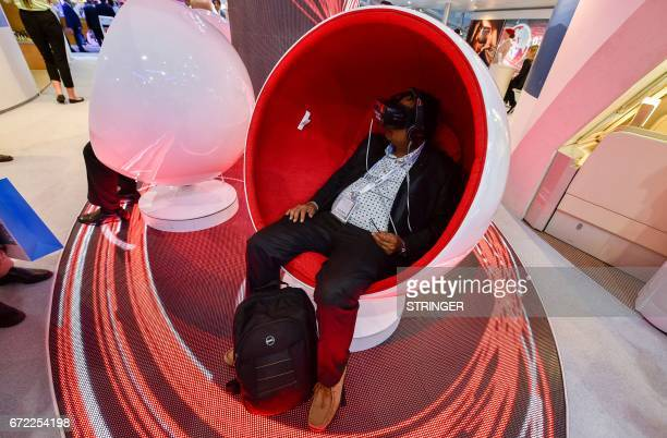 A visitor tries a virtual reality headset at the Emirates Airline pavilion during the Arabian Travel Market 2017 at the Dubai World Trade Centre on...