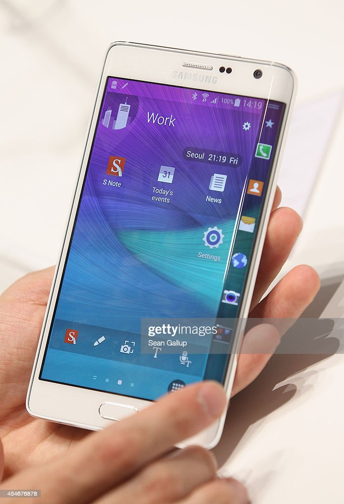 A visitor tries out a Galaxy Note Edge smartphone at the Samsung stand at the 2014 IFA home electronics and appliances trade fair on September 5 2014...