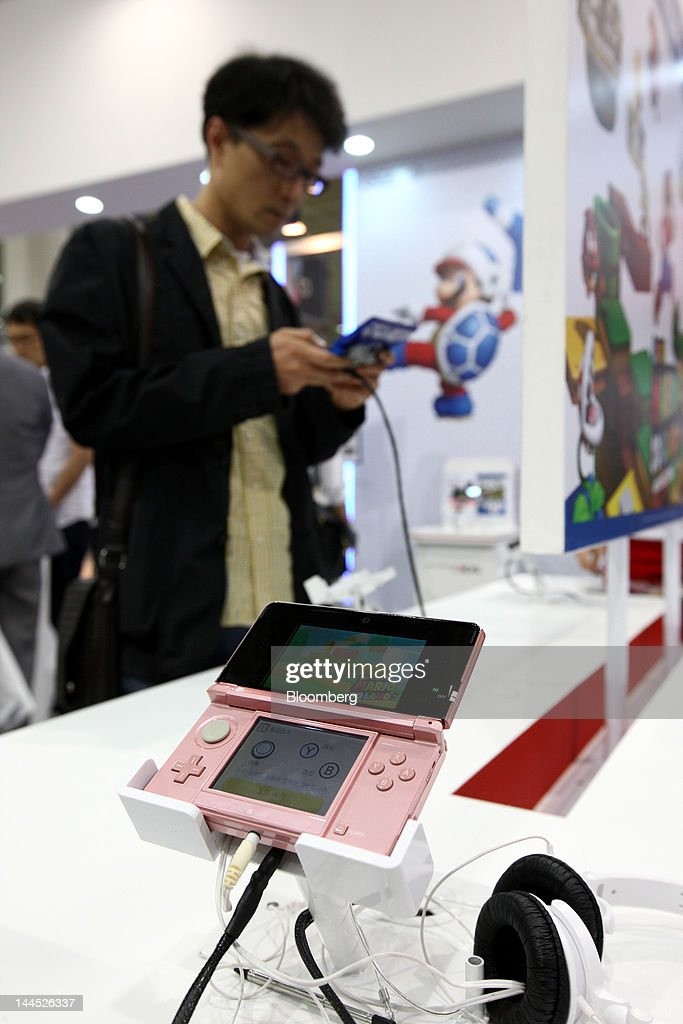 A visitor tries out a Nintendo Co. 3DS handheld game console in the company's booth at the World IT Show 2012 in Seoul, South Korea, on Tuesday, May 15, 2012. The show will be held through May 18. Photographer: SeongJoon Cho/Bloomberg via Getty Images