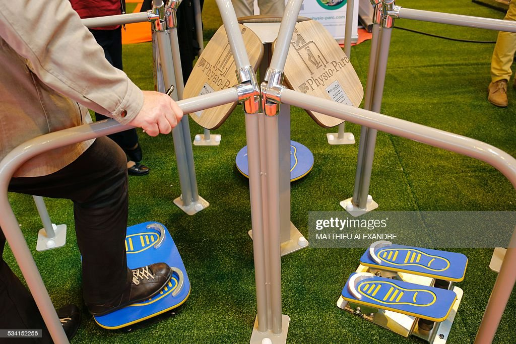 A visitor tries out a piece of equipment on display at a stand during Paris Healthcare week on May 25, 2016 in the French capital. / AFP / MATTHIEU