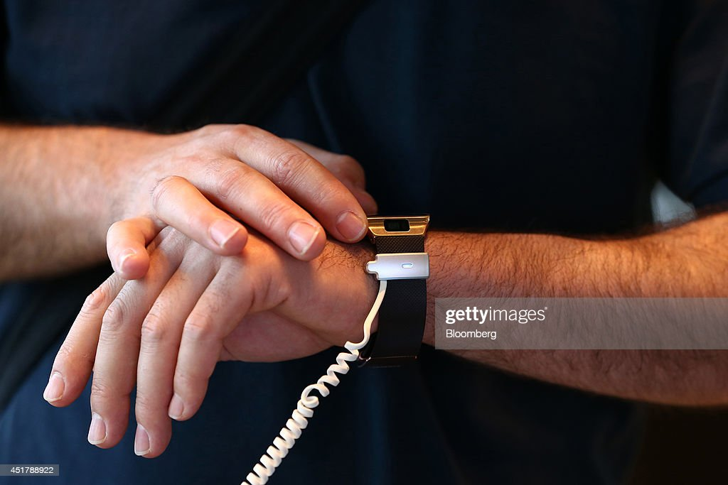 A visitor tries out a Samsung Electronics Co. Galaxy Gear 2 smartwatch at the company's d'light showroom in Seoul, South Korea, on Monday, July 7, 2014. Samsung Electronics is scheduled to report operating profit and sales figures on July 8. Photographer: SeongJoon Cho/Bloomberg via Getty Images