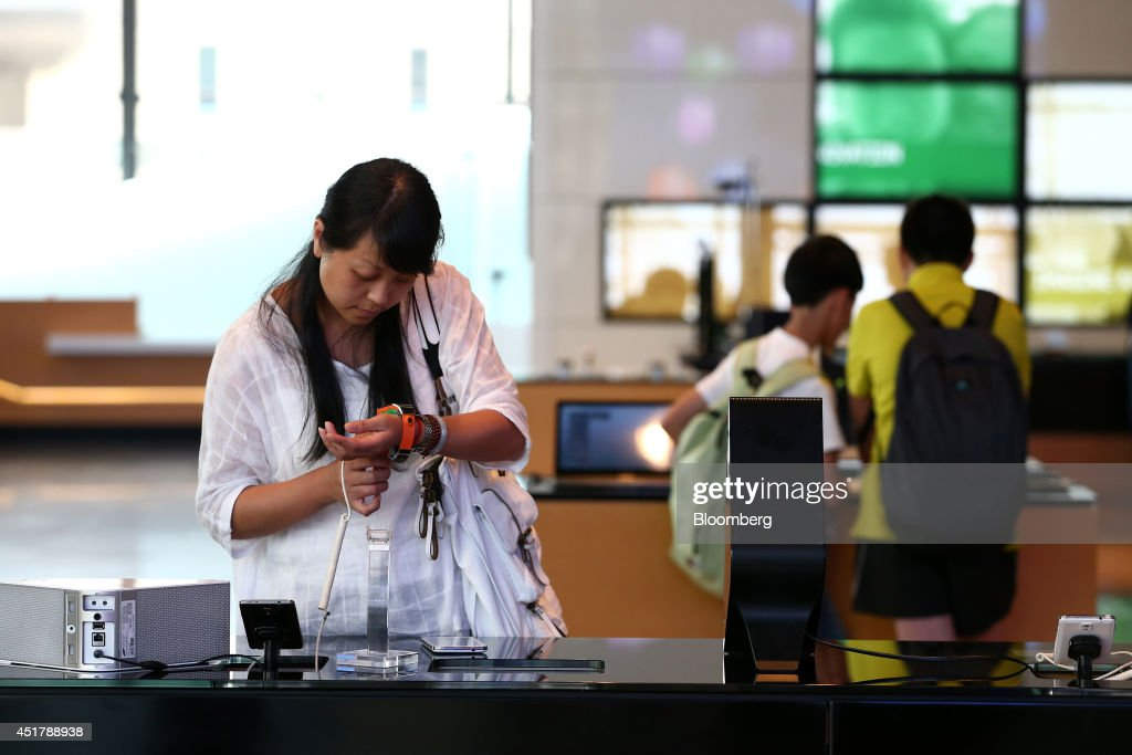 A visitor tries out a Samsung Electronics Co. Galaxy Gear smartwatch at the company's d'light showroom in Seoul, South Korea, on Monday, July 7, 2014. Samsung Electronics is scheduled to report operating profit and sales figures on July 8. Photographer: SeongJoon Cho/Bloomberg via Getty Images