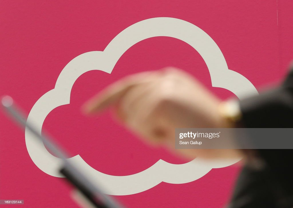 A visitor tries out a tablet computer next to a cloud computing and technology symbol at the Deutsche Telekom stand at the 2013 CeBIT technology trade fair on March 5, 2013 in Hanover, Germany. CeBIT will be open March 5-9.