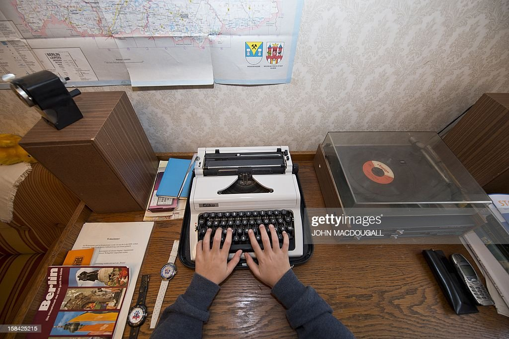 A visitor tries out a typewriter in the 'WBS70 apartment museum' in Berlin's Hellersdorf district December 16, 2012. WBS 70 refers to the 70th series of concrete slab construction type in the German Democratic Republic (DDR) which was first used in 1973. Furnished entirely with original east German fittings, the apartment museum, opened in 2004 when massive renovation schemes were about to be implemented in the area, and stands as a living memorial to everyday life and design in the former east Germany.