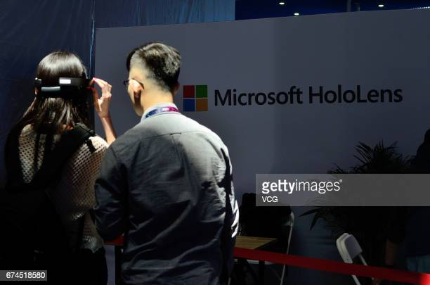 A visitor tries out a virtual reality headset Microsoft HoloLens during the Global Mobile Internet Conference 2017 at China National Convention...