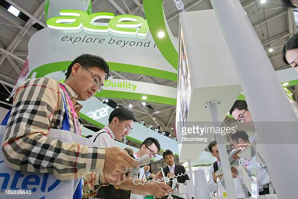 A visitor tries out an Acer Inc Iconia W3 tablet at the company's booth at Computex Taipei 2013 in Taipei Taiwan on Tuesday June 4 2013 Computex...