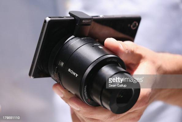 A visitor tries out an Xperia Z1 smartphone with a detachable camera lens at the Sony stand at the IFA 2013 consumer electronics trade fair on...