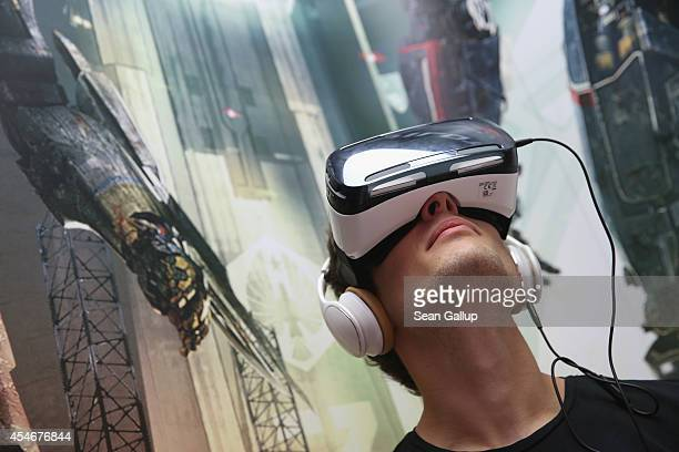A visitor tries out Gear VR virtual reality goggles amd headphones at the Samsung stand at the 2014 IFA home electronics and appliances trade fair on...