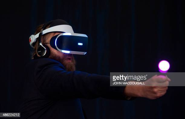 A visitor tries Sony's Project Morpheus virtual reality headset for PlayStation 4 at the booth of Japan's electronics giant Sony ahead of the opening...