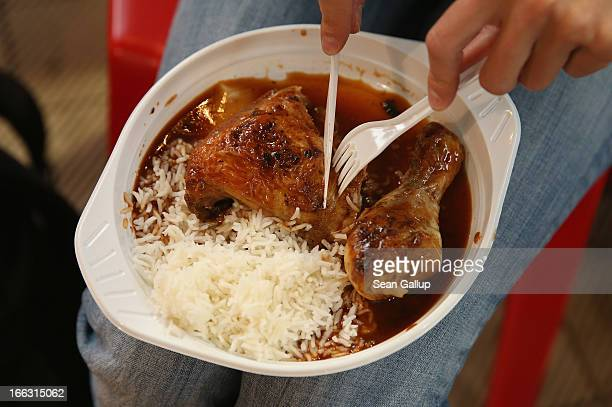 A visitor tucks into Caribbean jerk chicken on the first day of Street Food Thursday at the Markthalle Neun market hall in Kreuzberg district on...