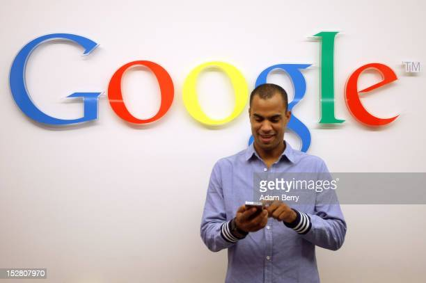 A visitor uses a cell phone in front of the Google logo on September 26 2012 at the official opening party of the Google offices in Berlin Germany...