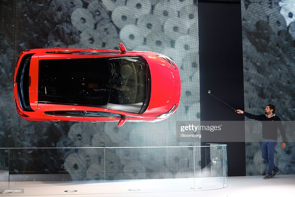A visitor uses a GoPro camera to photograph an Opel Corsa automobile produced by Adam Opel AG suspended on a wall during the preview day at the Paris...