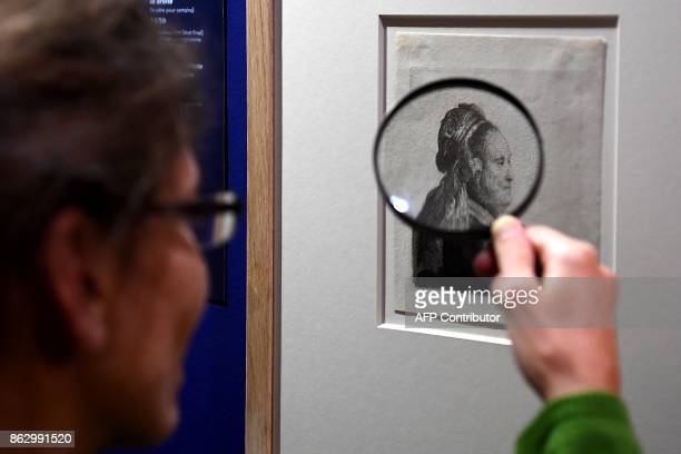 A visitor uses a magnifying glass to view an etching by late Dutch painter and printmaker Rembrandt during an exhibition of a complete collection of...