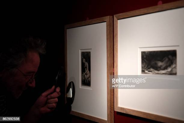 A visitor uses a magnifying glass to view 'Seated naked woman' and 'Black woman lying down' 1658 etchings by late Dutch painter and printmaker...