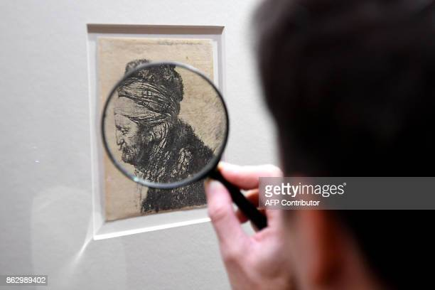 A visitor uses a magnifying glass to view 'The second oriental head' circa 1635 during an exhibition of a complete collection of 68 original etchings...